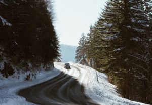 car driving on winter roads in heavily treed mountains