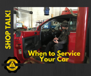 ASE Mechanic sitting in red VW Bug completing service check up