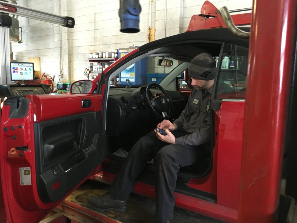 Zach checking the diagnostics on a red VW Beetle